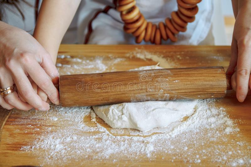 A child with his mother in the kitchen rolls out a dough, products from dough, flour, a bakery, bread. Master Class. Cook and learn stock images