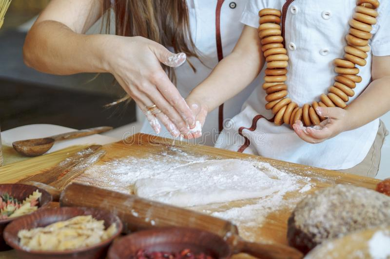 Child with his mother in the kitchen sprinkles flour dough. Products from dough, flour, bakery, bread. Master Class. cook and. Child with his mother in the stock photography