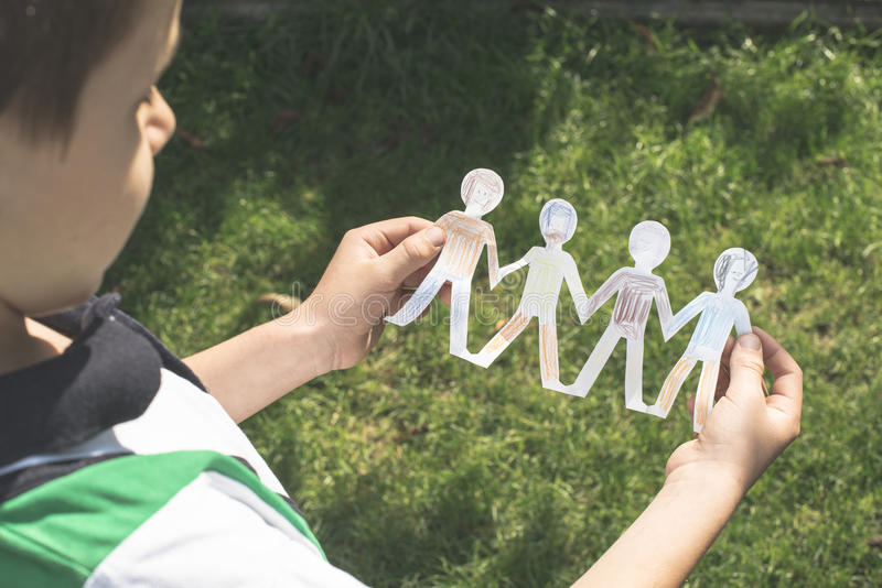 Child hold paper made people figures. Painted figures royalty free stock photos