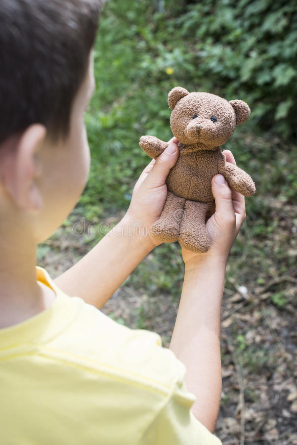 Child hold teddy in the hands. Child hold teddy in a garden royalty free stock photo