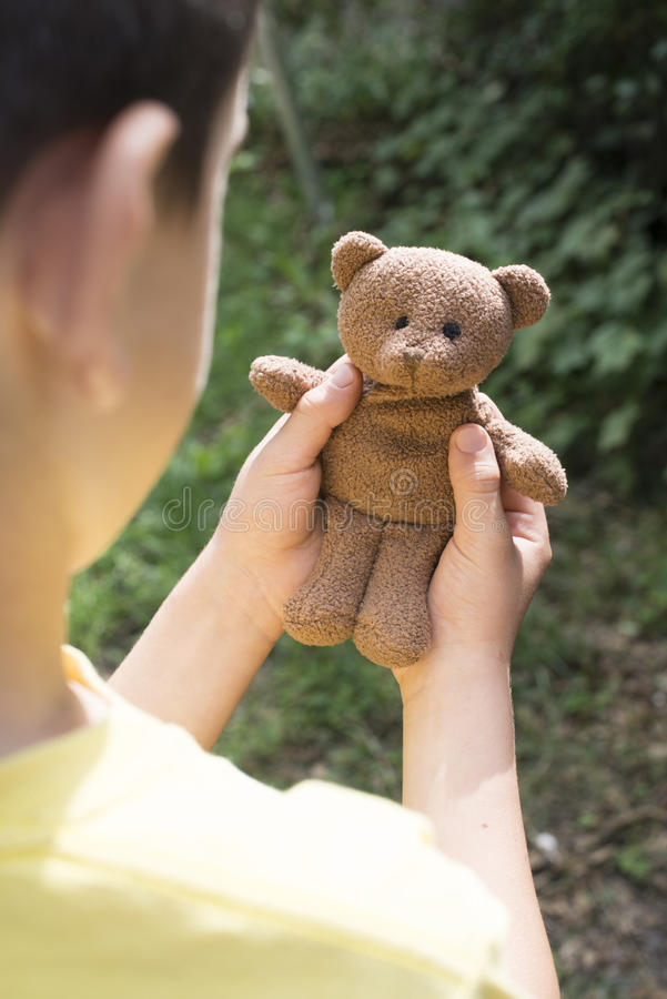Child hold teddy in the hands. Child hold teddy in a garden royalty free stock photos