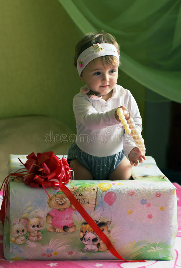 Child holding beads and standing in the box with a bow. Child holding beads and standing in the box with a red bow stock photo