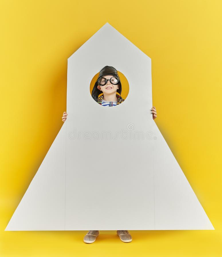 Child holding a big toy rocket royalty free stock photo