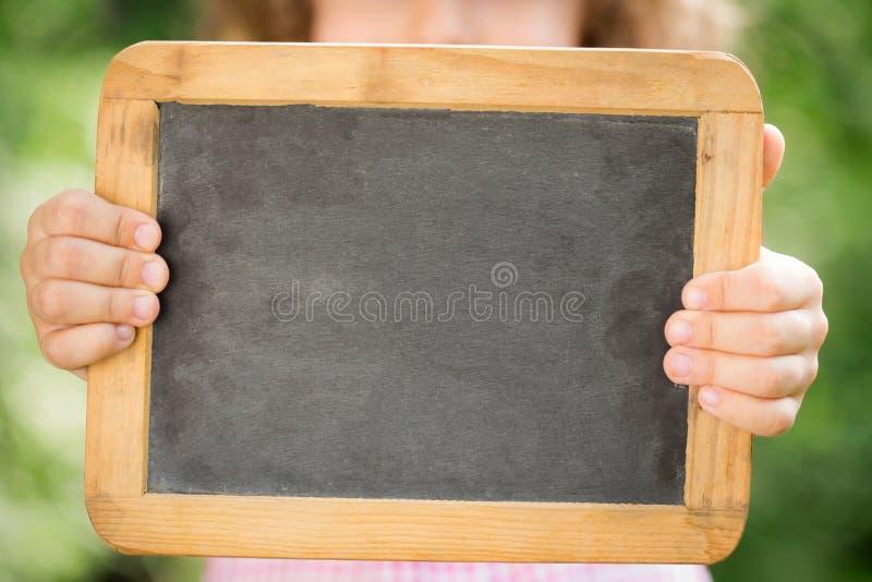 Child holding blackboard royalty free stock images