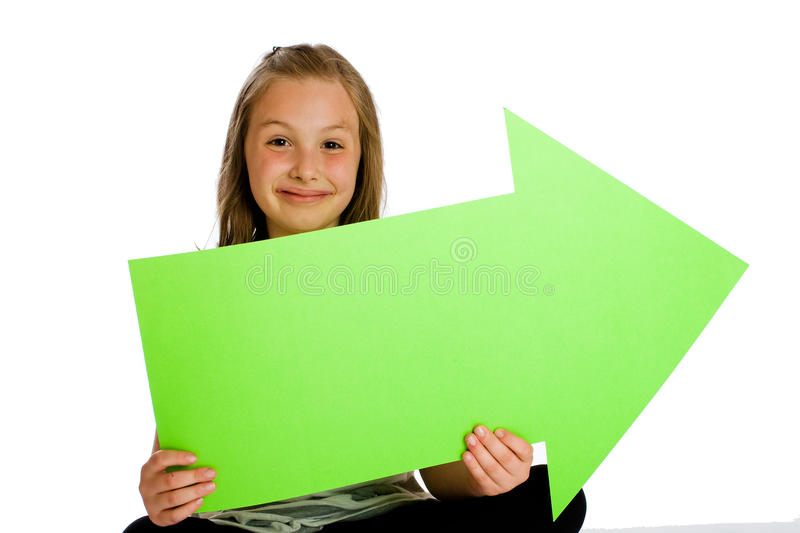 Child holding a blank green arrow sign. A cute young girl holding a blank green arrow sign in front of an isolated white background stock photography