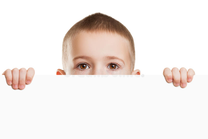 Child holding blank placard. Little scared or worried boy holding blank white sign or placard hiding face royalty free stock photos