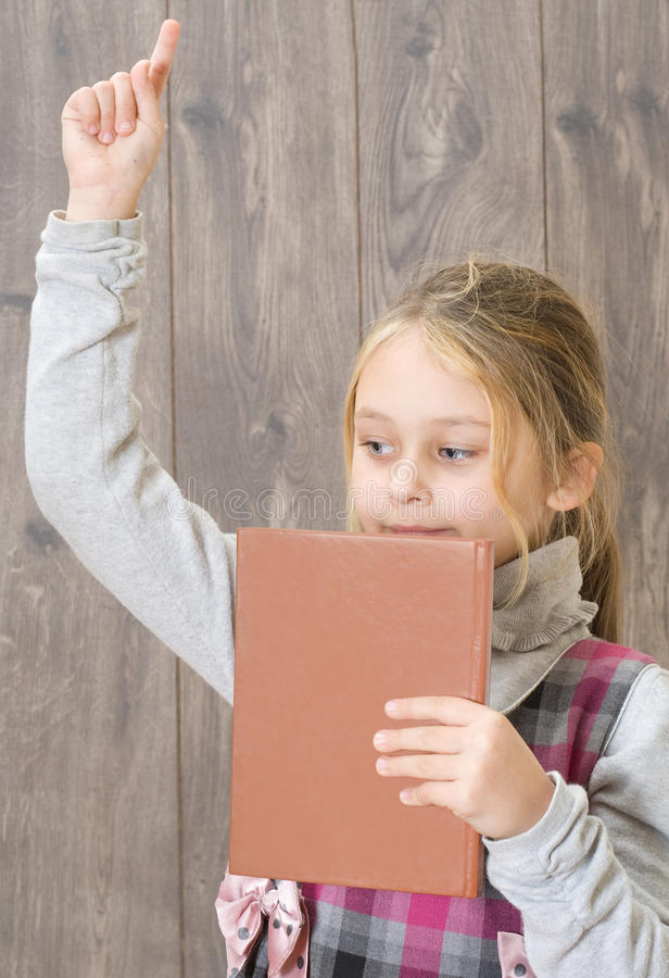 Child holding a book in his hand. And points his index finger upwards royalty free stock photos
