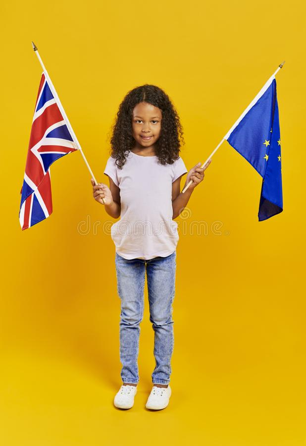 Child holding British and European Union flags. African girl holding British and European Union flags stock photo