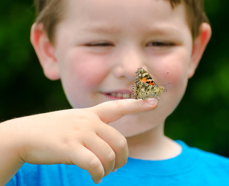 Child holding a butterfly. Spring concept with close up of a painted lady butterfly, Vanessa cardui, being held by child playing outdoors in nature stock photos