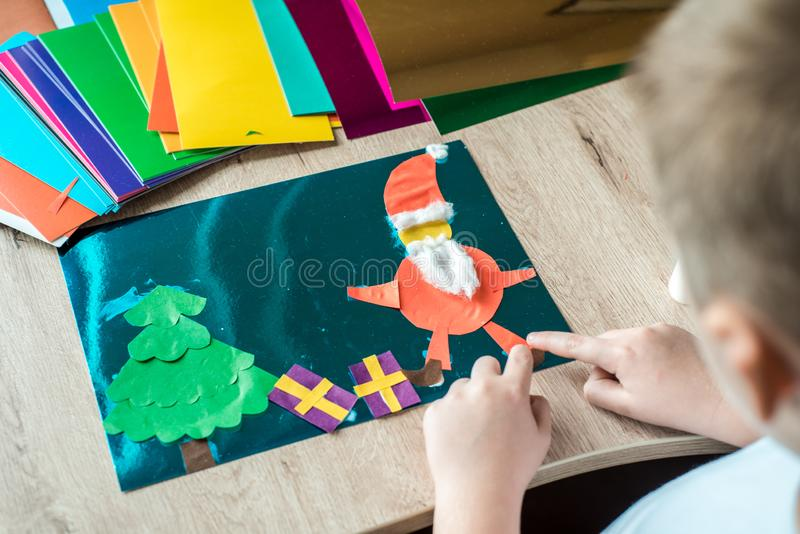 Child is holding a Christmas ball decor in his hands. Child is showing a Christmas ball decor. Simple recycled crafts and activiti. Es for kids. Christmas decor stock image