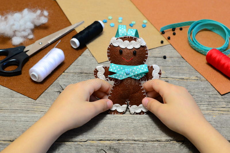 Child holding a cute gingerbread man ornament in his hands. Christmas tree gingerbread man ornament, handicrafts supplies royalty free stock photo
