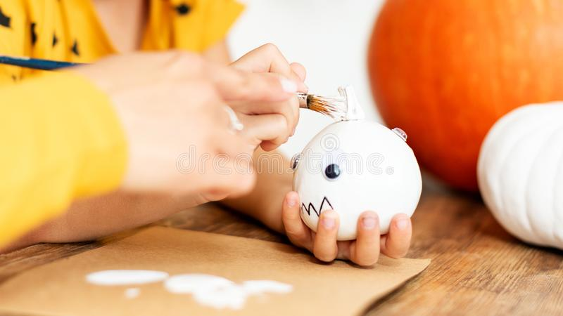 Child holding and decorating little white halloween pumpkin. Hands close up, cropped shot. stock images