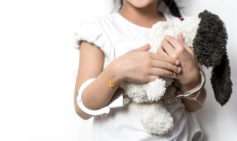 Child holding a doll with her hand in handcuffed stock photography
