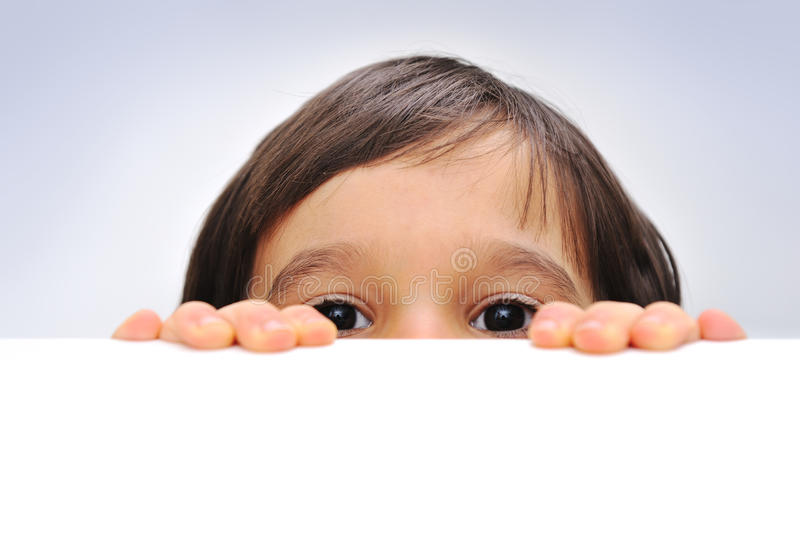 Child holding an empty sign. Over a white background, hiding behind royalty free stock images