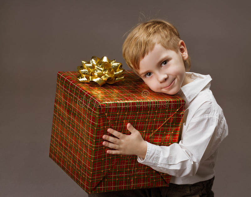 Child holding gift box. Boy with present stock images