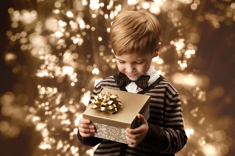 Child holding gift box, boy in vintage style. Child holding gift box. Boy in vintage style smart casual clothing, brown colors stock photo