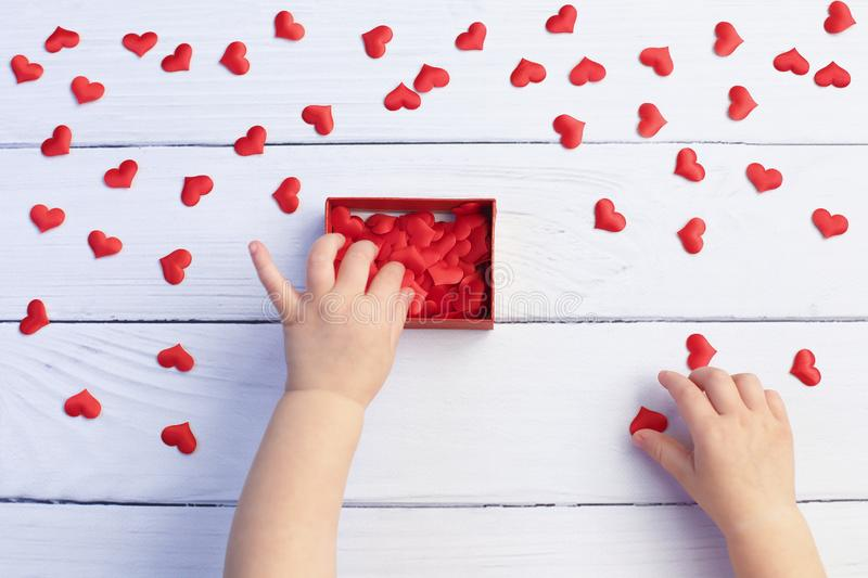 Child holding gift box and hearts for Mother`s Day on white wood background. Wedding and Valentine concept. stock photography