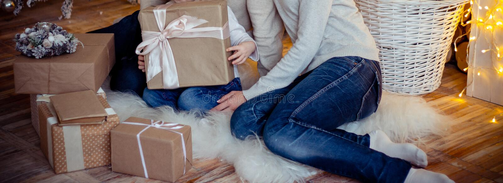 The child is holding a gift.family of three people, mom, dad and daughter, sitting on the floor, around the gifts, next to it ther. Family of three people, mom stock image