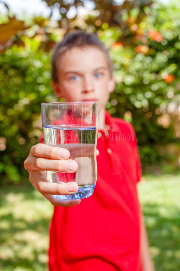 Child holding glass of drinking water outdoors stock photo