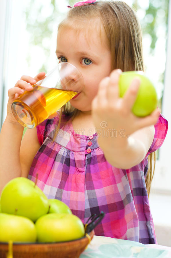 Child holding green apple and drinking juice royalty free stock photography