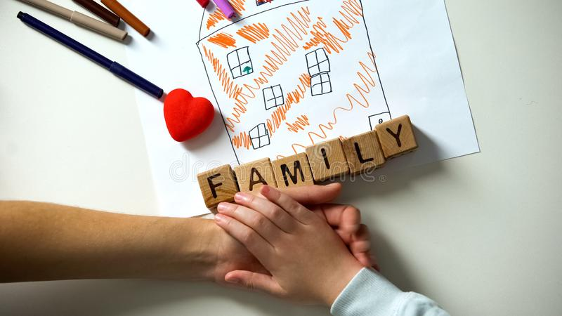 Child holding hand of adult person, family word made from cubes on house picture royalty free stock image