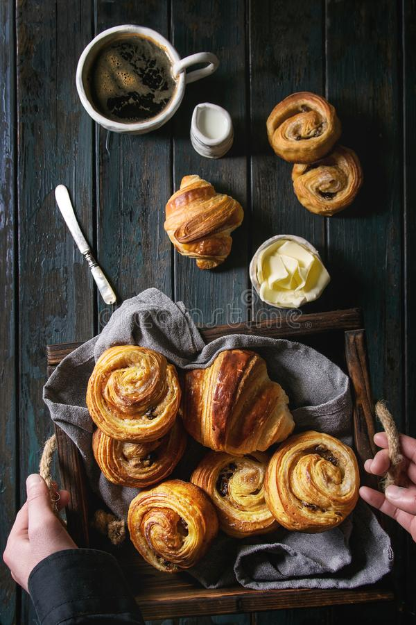 Puff pastry buns. Child holding in hands tray with variety of homemade puff pastry buns cinnamon rolls and croissant. Coffee cup, jam, butter as breakfast over royalty free stock photo