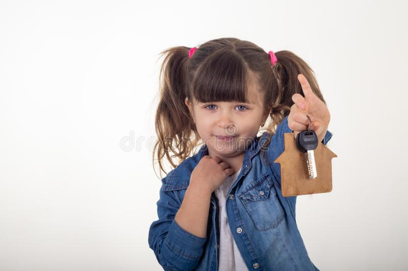 Child holding house keys on house shaped keychain like Real Estate Agent. stock photography
