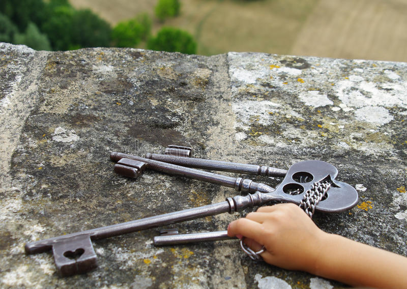 Child holding keys of medieval castle royalty free stock photo