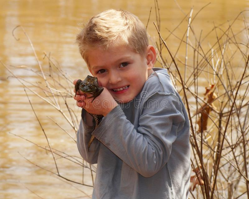 Child holding a large bullfrog. By a wetland pond stock photography
