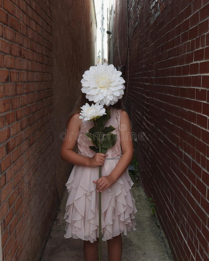 Child Holding Large White Flower in City stock photography