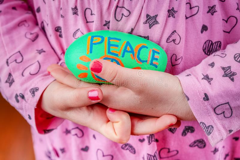 Child holding painted rock with the word Peace. royalty free stock photography