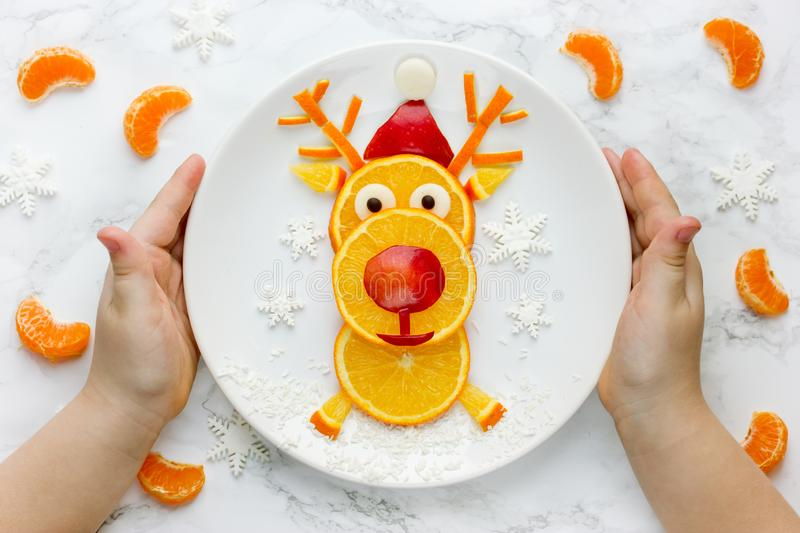 Child holding plate with edible fruit reindeer stock image