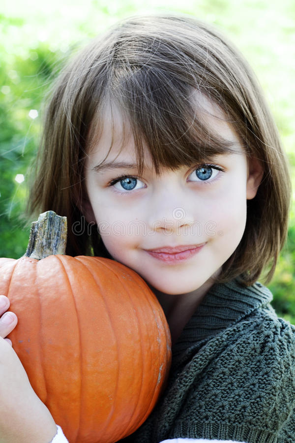 Child Holding a Pumpkin royalty free stock photo