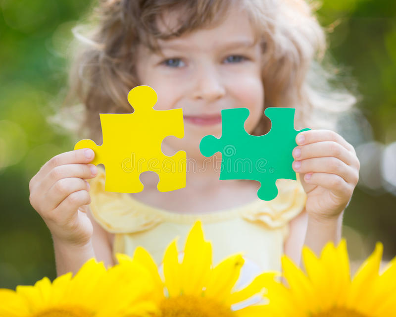 Child holding puzzles stock photo