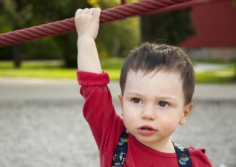 Child holding a rope. Portrait of a little boy with a hand on a rope in outdoor playground royalty free stock image