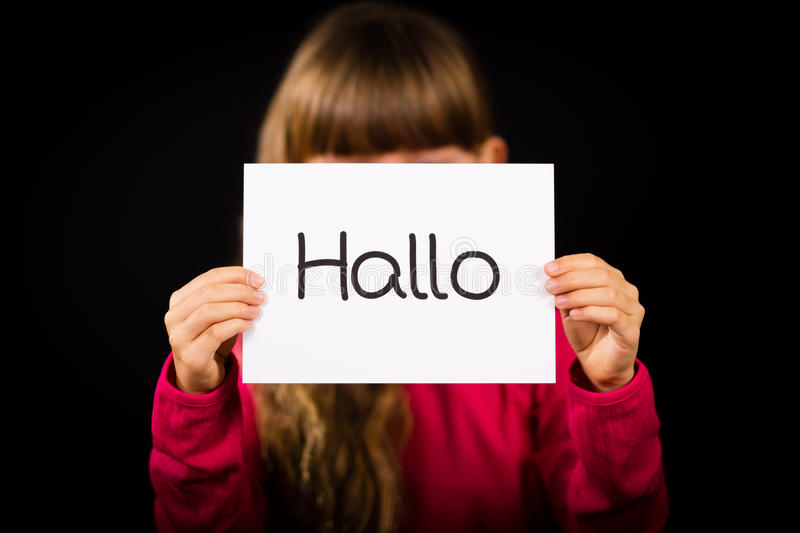 Child holding sign with German word Hallo - Hello in English. Studio shot of child holding a sign with German word Hallo - Hello in English stock image