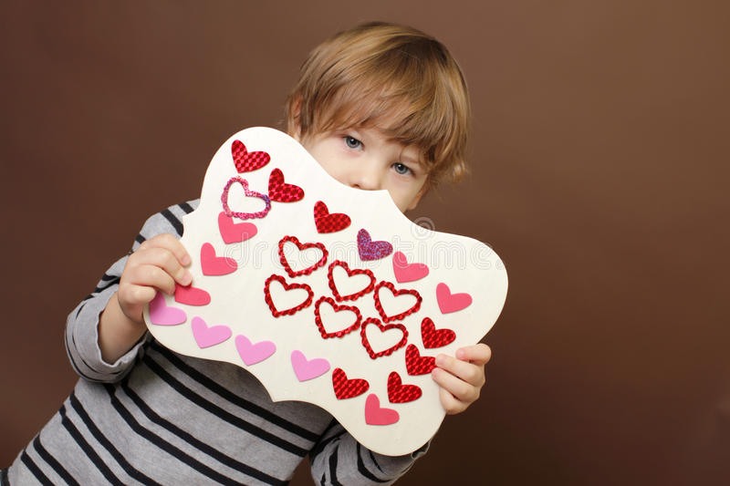 Child holding Valentine's Day Craft with Hearts royalty free stock photo