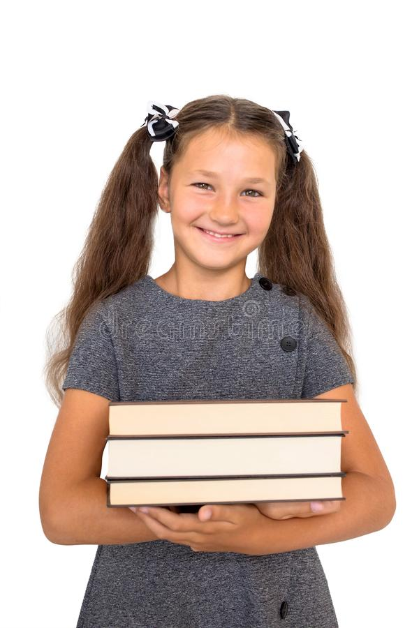Child holds books. Smiling schoolchild is ready for school. royalty free stock photo