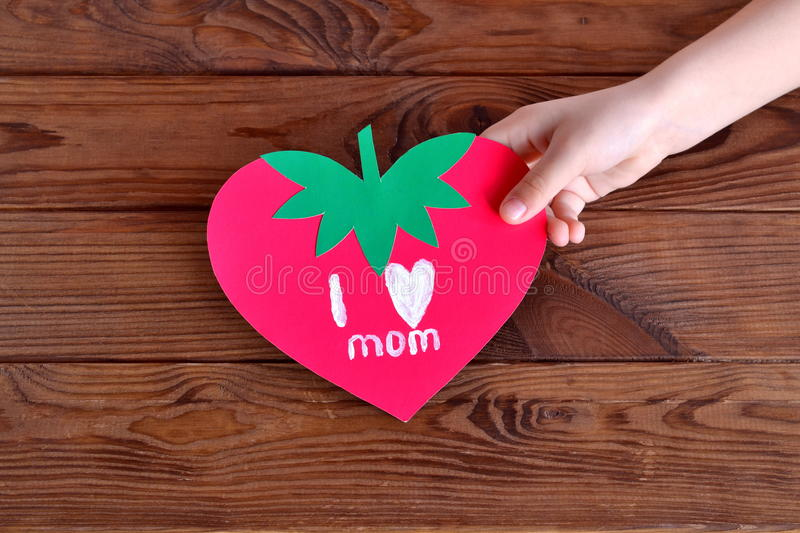 Child holds a card in his hand. Paper card strawberry. Greeting card mother's day. Original kids crafts stock photo
