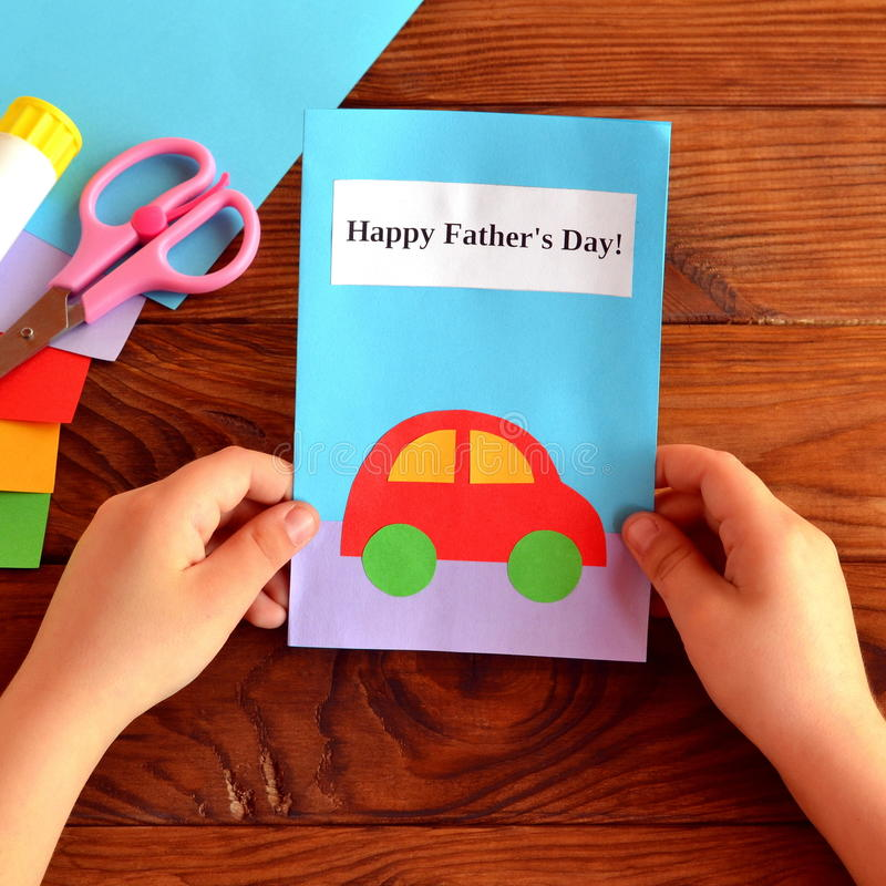 Child holds a card in his hands. Greeting card Happy father's day. Paper sheets, scissors, glue royalty free stock photos