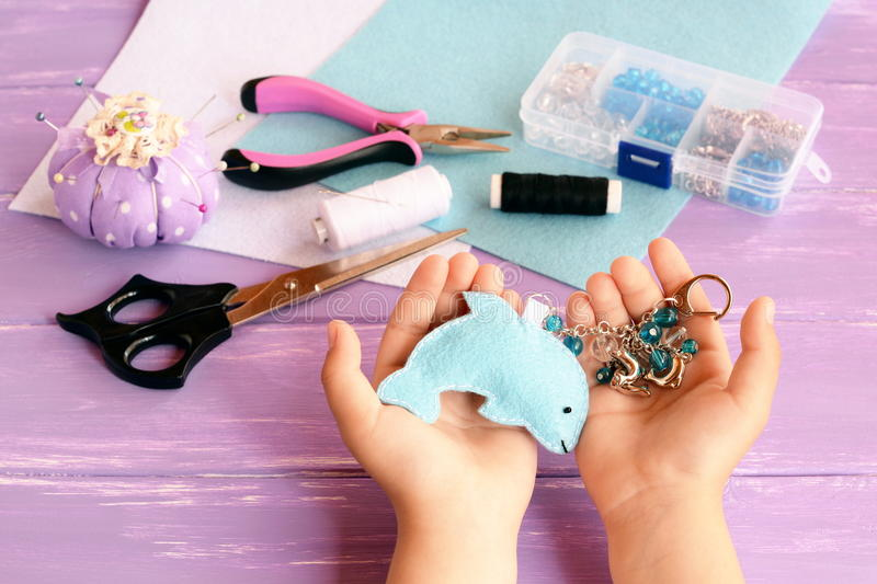 Child holds a felt dolphin toy in his hands. Home blue felt keychain with beads. Children sewing crafts concept. DIY stock photo