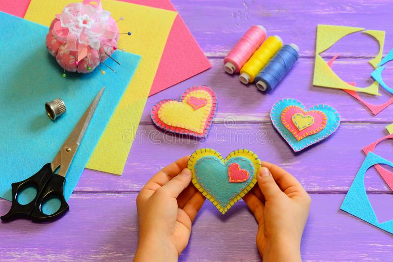 Child holds a felt heart gift in his hands. Child show a felt heart gift. Heart ornaments, scissors, felt sheets on a wooden table. Valentine`s Day heart crafts stock photos