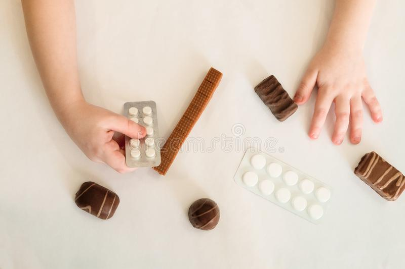 Child holds in hand a package of pills. Tablets are among the candies. Concept of dangerous domestic neighborhood medicaments and sweets. Top view royalty free stock photography