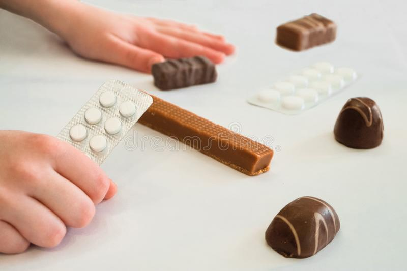 Child holds in hand a package of pills. Tablets are among the candies. Concept of dangerous domestic neighborhood medicaments and sweets. Limited depth of stock image