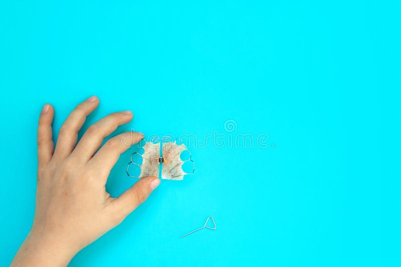Use orthodontic plate for baby s milk teeth to maintain proper bite. Child holds in his hand an anatomical orthodontic plate made of pink acrylic and metal in stock photography