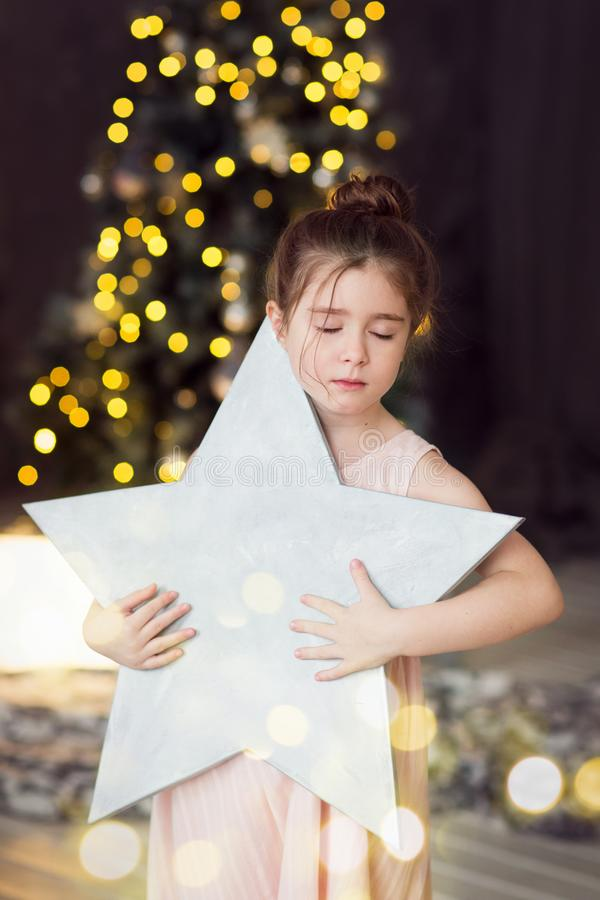 Child holds a star on the background of a Christmas tree.girl dreaming with eyes closed stock images