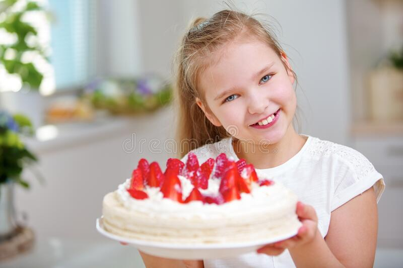 Child holds strawberry cake with fresh strawberries royalty free stock photos