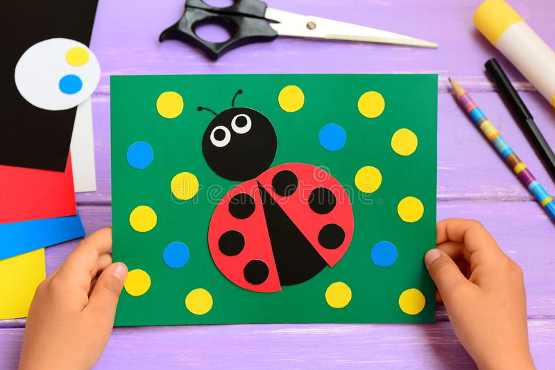 Child holds a summer card in his hands. Child made a paper ladybug card. Stationery on a wooden table. Easy paper circle crafts. Developing motor skills. Paper royalty free stock photos