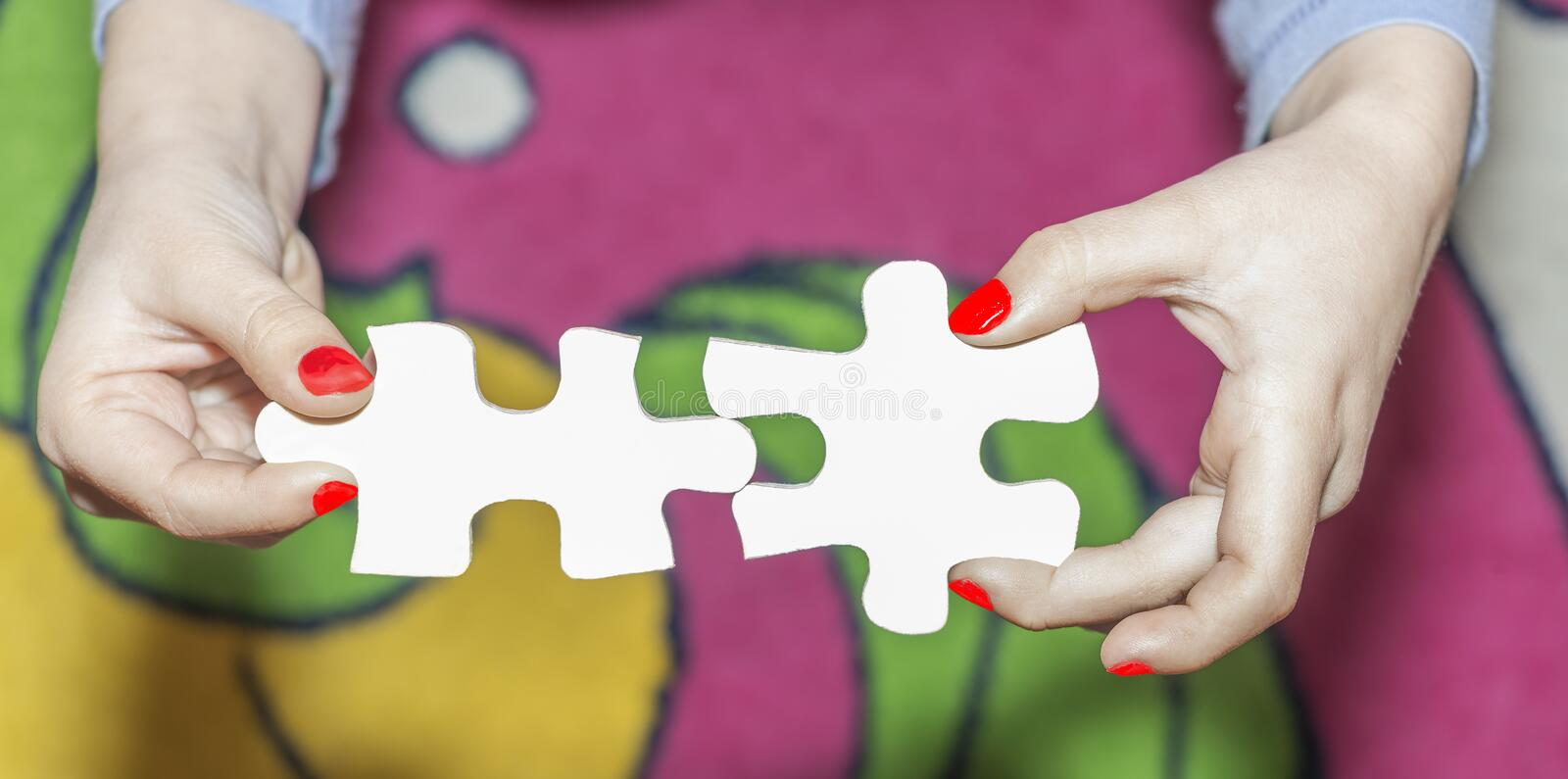 The child holds two parts of the puzzle stock images