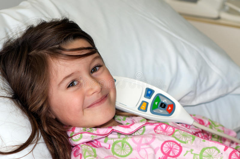 Child in hospital. Smiling happy little girl lying in hospital bed with nurse call system and patient entertainment handset control royalty free stock photos
